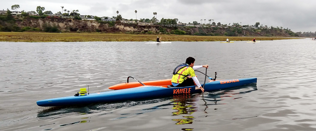 A blind kayaker paddling. The kayak has a motor on the back and a camera on the front.