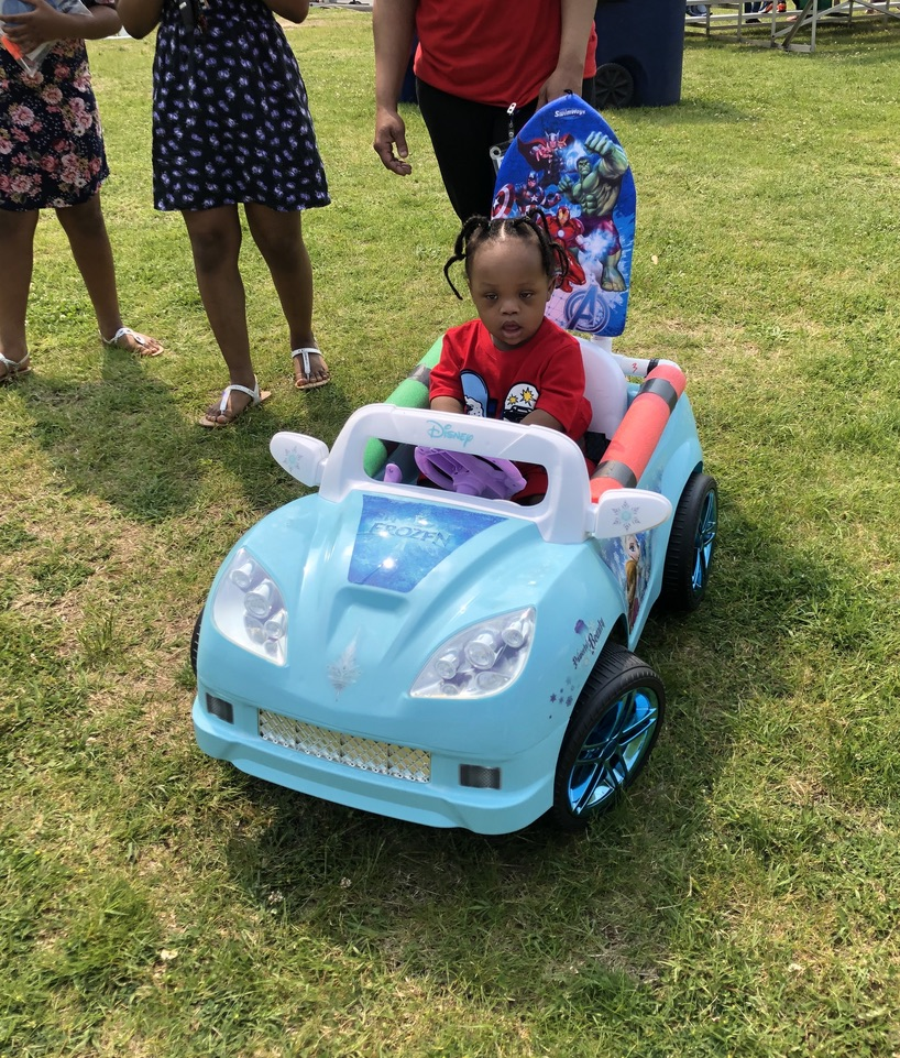 Girl driving toy car adapted by Go Baby Go