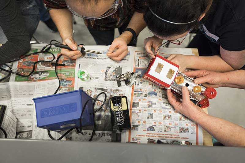 students soldering toys HuskyADAPT project