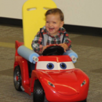 Toddler laughing and playing in a riding toy car adapted by Go Baby Go Seattle