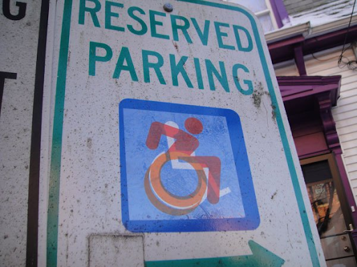The revised disabled symbol, a person with their arms back to go quickly in a manual wheelchair, in red shown on a parking sign over the old symbol.