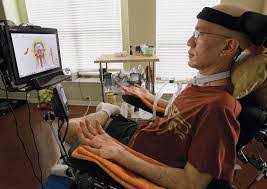 Digital artist Francis Tsai, an asian man, sitting in his wheelchair in front of a computer screen, where he is using eye gaze tools to create art. His left leg is crossed over his right, and his arms are supported by his wheelchair and his palms are facing up. There are two windows with blinds drawn in the background.