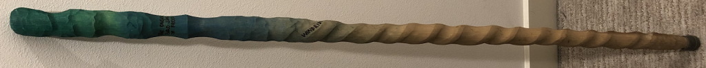 A handcarved cane with a spiral design and painted green at the top
