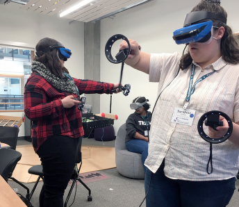 Two student participants at the 2019 OurCS workshop use virtual reality goggles and hand controllers