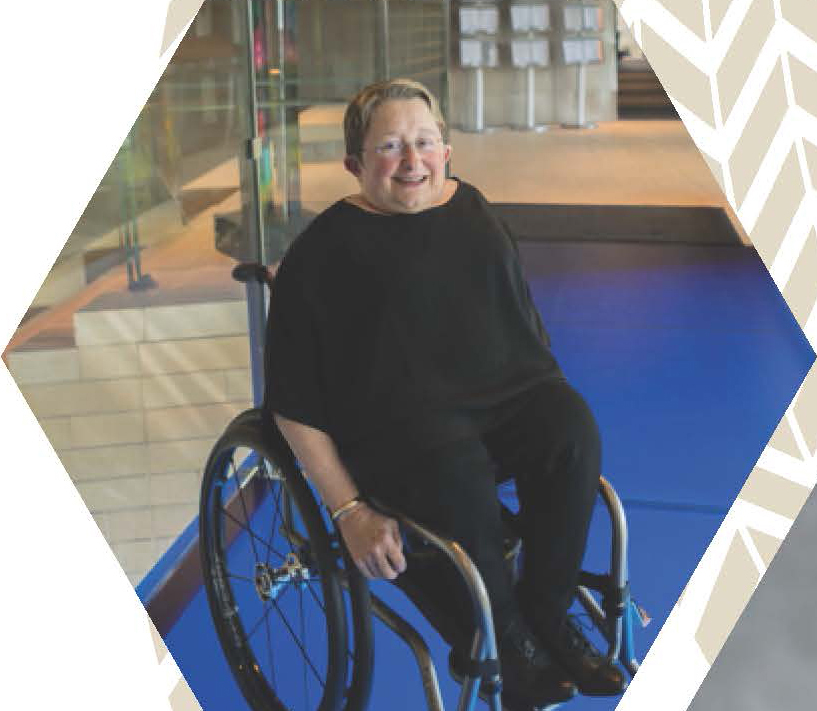 Karen Braitmayer using a wheelchair in a modern building with stairs and ramps