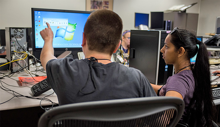 Two students work together in a lab on a computer screen using accessibility tools